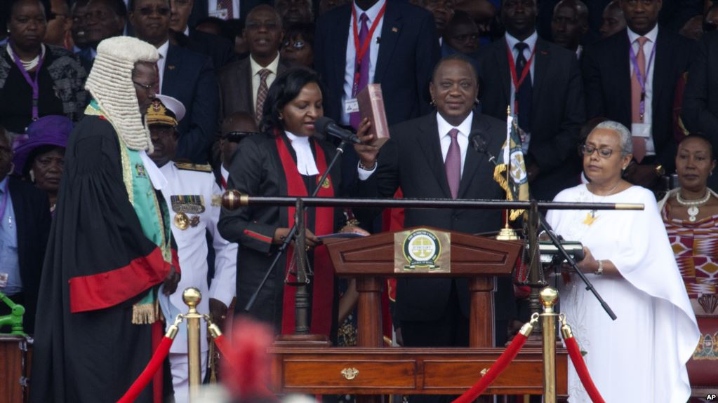 Kenyan President Uhuru Kenyatta, center, is sworn in as his wife, Margaret, right, looks on during his inauguration at Kasarani Stadium in Nairobi,Kenya, November 28, 2017. (AP)