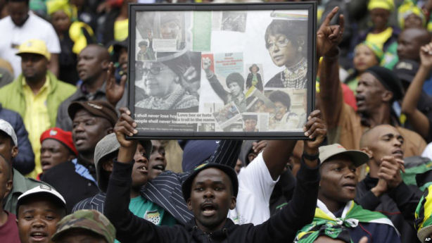 A man holds up a frame showing newspaper clippings of anti-apartheid activist Winnie Madikizela-Mandela during her memorial service at Orlando, Stadium, in Soweto, April 11, 2018. (AP)