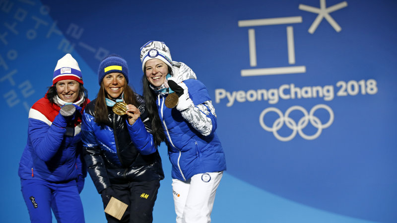 The first medals of the 2018 Winter Olympics, in the women's cross-country 15-kilometer skiathlon, were won by (from left) Norway's Marit Bjoergen, silver; Sweden's Charlotte Kalla, gold; and Finland's Krista Parmakoski, bronze. (AP/Patrick Semansky)