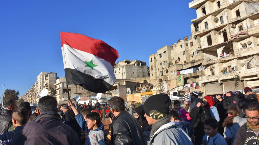 A young boy waves the Syrian flag as residents in a government held area of Aleppo gather in the street during an evacuation operation of rebel fighters and their families from rebel-held neighborhoods in Syria's northern embattled city on December 15, 2016. (AFP)