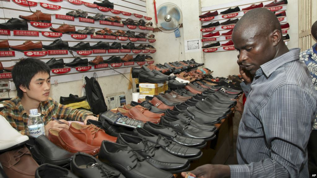 A Chinese shoe-seller, watches as a customer inspects his wares, at a shoe shop in Kampala, Uganda, (AP)