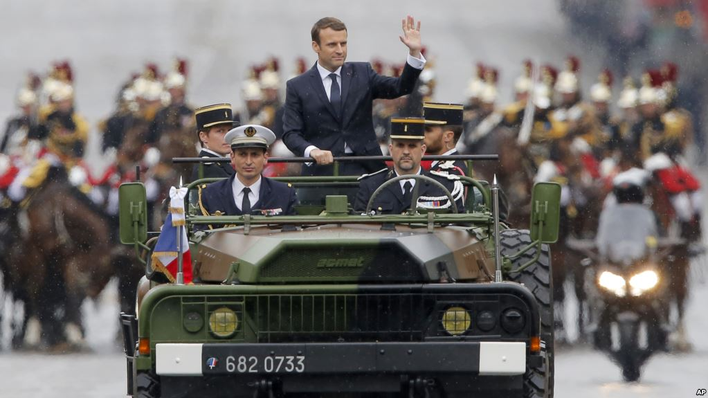 New French President Emmanuel Macron waves from a military vehicle as he rides on the Champs Elysees avenue towards the Arc de Triomphe in Paris, May 14, 2017. (AP)