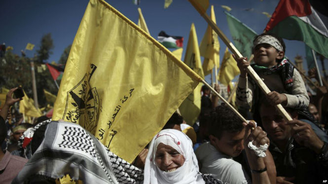 Palestinians wave national and yellow Fatah movement flags during a rally marking the 13th anniversary of the death of Fatah founder and Palestinian Authority leader Yasser Arafat, in Gaza City. November 11, 2017. (AP)
