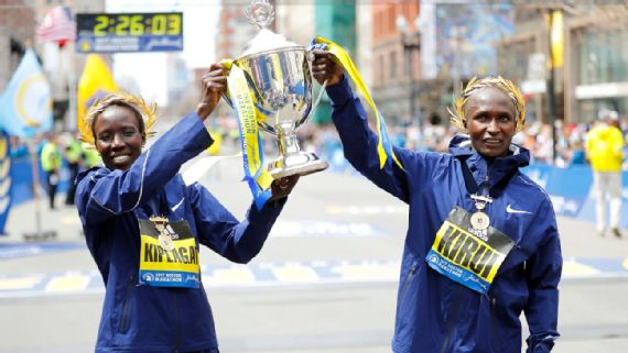 Edna Kiplagat (left) and Geoffrey Kirui, both of Kenya, raise the trophy after winning the women's and men's races at the Boston Marathon. April 17, 2017. (USA Today/Winslow Townson)