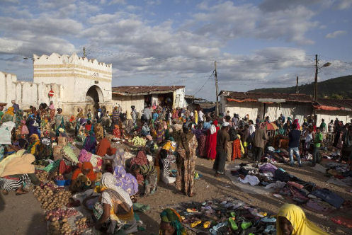 People gather at a market set up in front of the Shoa Gate, one of the five historic gates of the ancient walled city of Harar, Ethiopia, on August 3, 2014 (AFP/Zacharias Abubeker)