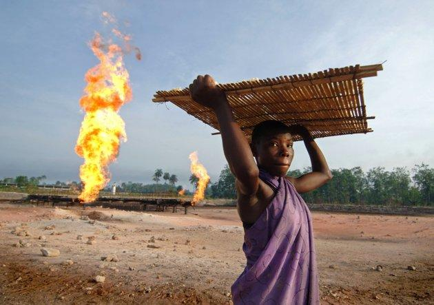 A woman carries tapioca seeds next to a gas flare fire near the Niger Delta port city of Warri. Shell has begun looking at a potential $4.0 billion in new projects in Nigeria to boost production and reduce the amount of gas burned off into the atmosphere, the company's chief executive has said. (Photo AFP/Lionel Healing)