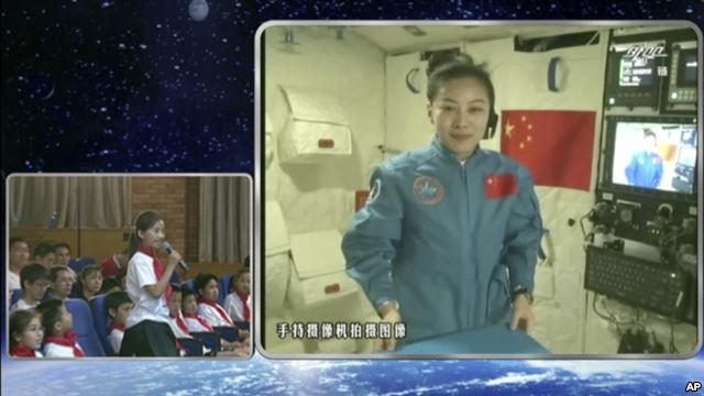 Chinese astronaut Wang Yaping, seen on screen, listens to a question from a school girl in Beijing, China during a live broadcast from Tiangong-1 space laboratory, June 20, 2013. (AP/ CCTV)