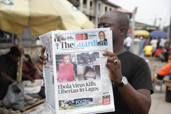 A man reads a newspaper on a Lagos street with the headline Ebola Virus kills Liberian in Lagos, July 26, 2014. (AP/Sunday Alamba)