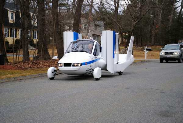 Terrafugia's flying car, dubbed the Transition, travels down a street with its wings folded. The vehicle has two seats, four wheels and wings that fold up so it can be driven like a car. It flew at 1,400 feet for eight minutes during its test flight on March 23.  (Photo Terrafugia)