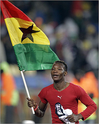 Ghana's John Pantsil runs with his country's flag at the end of the World Cup round of 16 soccer match between the United States and Ghana at Royal Bafokeng Stadium in Rustenburg, South Africa, on Saturday, June 26, 2010. (Rick Bowmer/AP Photo)