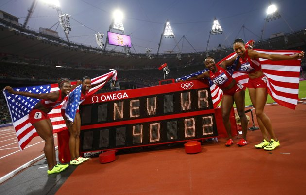 Members of the U.S. team pose with their national flags by the scoreboard after winning the women's 4x100m relay final during the London 2012 Olympic Games at the Olympic Stadium August 10, 2012. The team, made up of (from L to R) Tianna Madison, Carmelita Jeter, Bianca Knight and Allyson Felix, set a new world record with a time of 40.82 seconds. (Photo Reuters/Kai Pfaffenbach)