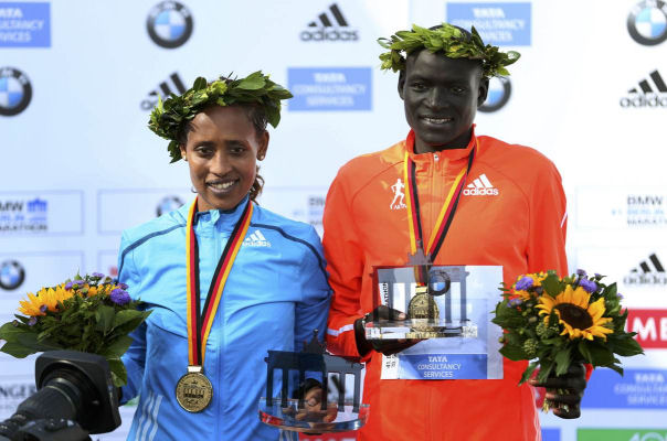 Tirfi Tsegaye of Ethopia and Dennis Kimetto of Kenya (R) celebrate during the awards ceremony after winning the 41st Berlin marathon, September 28, 2014. (Reuters/Hannibal Hanschke)